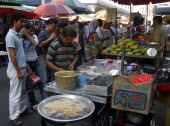 Market stalls selling various foodstuffs with customers waiting for hot food in the foreground
