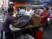 Market stall selling hot snacks cooked in a large wok with vendor and customers