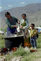 Woman heating milk in large pot at the 14th Dalai Lamas birthday celebrations