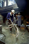 Elderly man cutting firewood for the kitchen in a courtyard