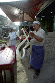 Man spinning dough at a street side stall