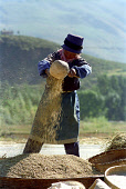 Woman pouring grain that she has ground in a ceramic dish