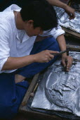 Tha Phae Road.  Young man working on metal work relief picture.Asian Prathet Thai Raja Anachakra Thai Siam Southeast Asia Immature Male Men Guy Siamese Male Man Guy Young Unripe Unripened Green