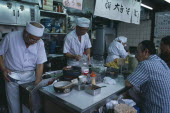 Tsukiji Fish Market. Chefs working in the open kitchen of a food bar with customers sitting at the counter