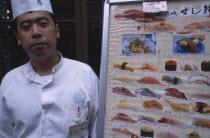 Tsukiji Fish Market with chef standing beside seafood menu board