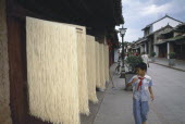 Weishan. Racks of noodles hanging out to dry in street with a boy walking past on pavement.