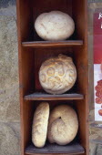 Traditional breads displayed on wooden shelves.