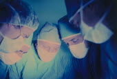 Operating theatre with five medical staff wearing surgical masks looking down towards patient