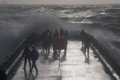 Waves crashing over a groyne with people on it