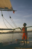 Felucca on the River Nile in the evening with young boy adjusting riggingChild labour