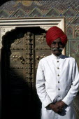 Palace guard dressed in white and wearing a red turban standing by ornate doorway