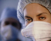 Portrait of female member of surgical team wearing mask and cap