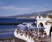 Playa de las Americas. Terraced bar overlooking the beach with customers sitting at table and a man standing on a balcony above