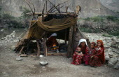 Kirghiz woman and children sitting outside tent while another woman cooks over wood fire inside.