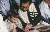 Jewish father and son attending preparation for Bar Mitzwah in synagogue.