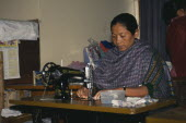 Tribal lady working at sewing machine.textiles