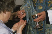 Woman holding out cupped hands to receive the host from priest during Anglican service.  Cropped view.consecrated bread or wafer