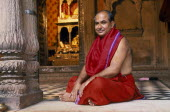 Hindu priest in red robes sitting cross legged on temple floor.