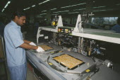 Man working in a factory producing circuit boards.