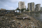 Polluted shoreline covered with rubbish with shanty housing and high-rise buildings behind.