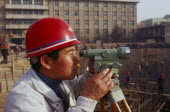 Surveyor using a theodolite working on a building construction site.