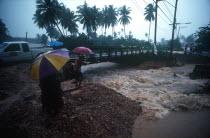 Torrent of flood water beneath bridge  watched by people with umbrellas.