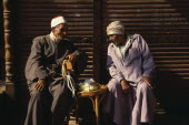 Two old Muslim men seated  in conversation.
