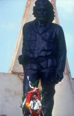 Young child at memorial day with statue of Che Guevara behind