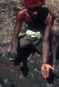 Gem miner displaying gems in one hand and unpanned mud in other.