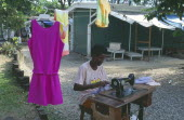 Dressmaker working outside at hand operated sewing machine.