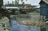 Wani. Housing next to street with river running through it contaminated with rubbish.  Near Palu