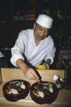 Sushi chef preparing dish.