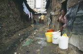 Village One residents in the narrow alleys of the notorious no go slum without sanitation being cleaned up by residents after cholera outbreaks