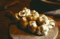 Garlic lying on wooden board on table.