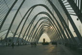 Olympic Stadium. People wandering through the walkway covered with arches in the evening.