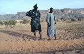 A Diviner and Dogon client explains marks left in sand by desert fox over the marks he made the day before.