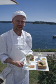 Magnus Ech owner and chef holding a tray of food at Oaxen Skargards Krog restaurant