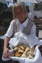 Smiling woman holding a basket of Swedish bread at Oaxen Skargards Krog restaurant
