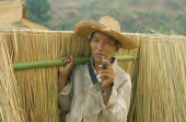 Akha man smoking bamboo pipe whilst carrying grasses collected for roofing