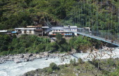 Nepal, Annapurna Region, Transport, Suspension bridge over fast flowing river near Bhubhule with two trekkers crossing.