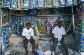 Tanzania, Zanzibar Island, arts and crafts, two young men in open fronted shop selling  paintings in the Tingatinga style depicting african animals in bold colours.