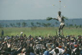 Stilt walker above crowds at Bapende tribe Gungu Festival. Pende