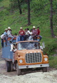 Ford truck full of campesino men climbing a steep incline.