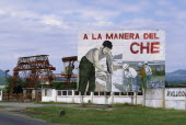 Billboard celebrating the work of Che Guevara  with industrial facilities behind.