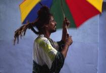 Rastafarian man on stilts  with umbrella as part of street parade