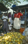 Fruit stall in the market with two female vendors and two children
