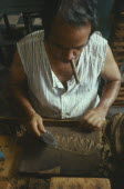 Man smoking a cigar whilst he rolls cigars in a cigar factory