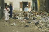 School children walking past rubbish dump with chickens and dogs scavenging in the City of the Dead