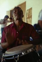 Man playing tall bongo type drum with his handsPercussion InstrumentDrumsCaribbean Cuban Trini Trinidadian West Indies Hispanic Latin America Latino Male Men Guy American Male Man Guy