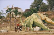 Parco Prehistorico dinosaur replicas with man on horseback riding past